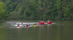 Kayaks and rafters paddle in river Stock Footage