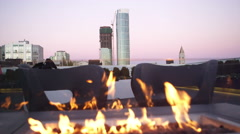 A fire pit burns on top of a roof bar as two women enter the scene - stock footage