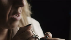 A woman is praying with rosary beads:reciting prayers, tradition, Catholic Stock Footage