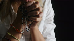 woman is praying on dark background with rosary beads: cross, religion, God - stock footage