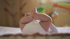 The baby is lying on the bed and funny moves legs, unusual sight Stock Footage