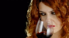 beautiful red haired woman drinking red wine isolated in dark background - stock footage