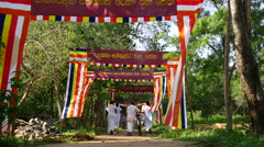 People walking in white cloths to a buddism temple in Sri Lanka Stock Footage