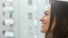 Portrait of a beautiful smiling brunette at the window, close up HD - stock footage