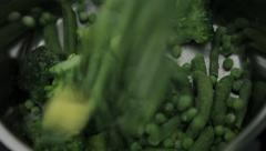 Frozen green vegetables falling in cooking jar Stock Footage