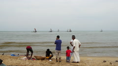 Family watching a fisherman work at the beach Stock Footage