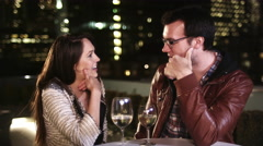 A man and a woman sit at a table with drinks and flirt and talk at night Stock Footage