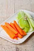 bundle of fresh green celery stems and carrot - stock photo