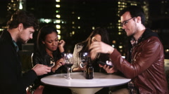 Four people sit at a table but ignore each other while they are on their phones Stock Footage
