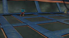 KID IN A HUGE ROOM OF TRAMPOLINES Stock Footage