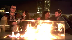 Four friends hanging out on a rooftop bar at night sit in front of a fire pit Stock Footage