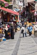 Locals and tourists mingle in the backstreet market Stock Photos