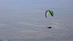 A paraglider paragliding over a green landscape Stock Footage