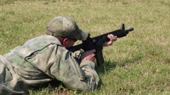 Closeup of Isolated Man Firing from Lying and Kneeling Position Stock Footage