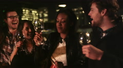 A group of friends hang out on a rooftop bar at night, dancing and laughing - stock footage