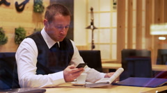 Businessman typing sms regarding advertisement in the cafe, steadycam shot Stock Footage