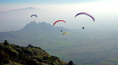 Paragliding over the mountains against clear blue sky Stock Footage