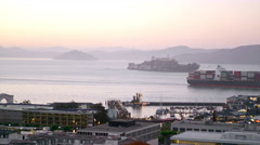 A cargo ship cruises past Alcatraz as seen from a bay in San Francisco Stock Footage
