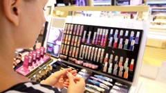Woman Buying and Testing Lipstick in a Cosmetics Store. Stock Footage