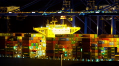4K cargo container hoisting cranes loading ship harbor traffic night timelapse Stock Footage