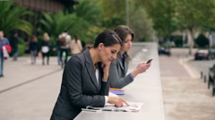 Businesswomen having break and relaxing on public square Stock Footage