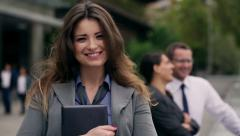 Businesswoman using tablet and smiling to the camera on public square Stock Footage