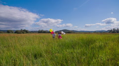 Two kids with balloon running to the camera  - stock footage