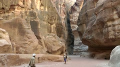 Jordan historical and archaeological city Petra 020 citizen walk through a gorge Stock Footage