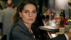Businesswoman doing serious look to the camera in the pub, steadycam shot Stock Footage