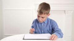 Beautiful, caucasian boy draws a pencil on the album Stock Footage