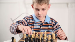Beautiful boy playing chess on a bright background Stock Footage