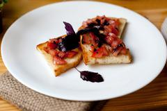 Appetizer with tomatoes and basil on toasted bread Stock Photos