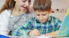 Little boy doing homework, mum checking on him Stock Footage