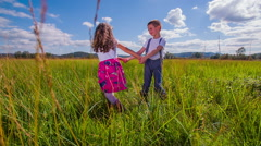 Brother and sister playing on a grass field, spinning around - stock footage