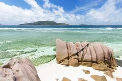 anse banane in la digue, seychelles with clear water and granite rocks - stock photo