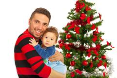 Funny father and his son near Xmas tree - stock photo