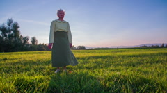 Wind blows old woman skirt while she is standing on a field at sunset Stock Footage