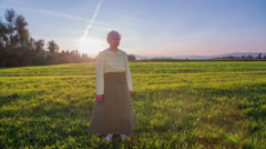 Old senior woman standing on a field at sunset Stock Footage