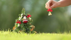 Girl hangs third bell on the Christmas tree Stock Footage