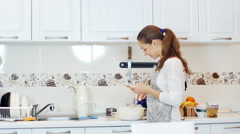 Happy young woman sending sms in the kitchen  Stock Footage