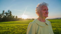 Face with wrinkles of an old woman at sunset Stock Footage