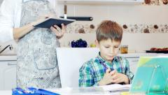 Mother standing in the kitchen with tablet computer. and son doing homework Stock Footage