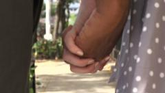 An interracial couple walk in slow motion, holding hands. - stock footage