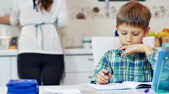 Little boy doing homework in the kitchen with his mother Stock Footage