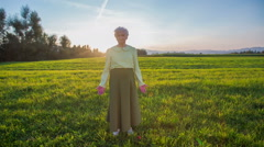 Old granny standing on lawn with sunset in backgrond - stock footage