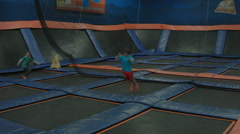 KID JUMPS & BOUNCES ACROSS A GIANT ROOM OF TRAMPOLINES Stock Footage