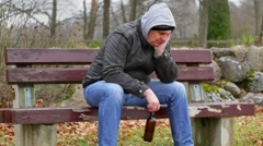 Sorrowful man with beer bottle on the bench - stock footage
