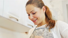 Beautiful woman using her smartphone standing in the kitchen  Stock Footage