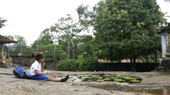 Boy sitting by a pond with lotus flowers close to a temple Stock Footage