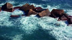 Deep green sea waves crashing on dark red rocks Stock Footage